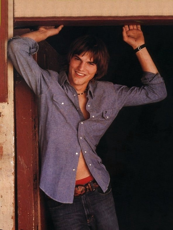 un sorridente Ashton Kutcher in camicia sbottonata