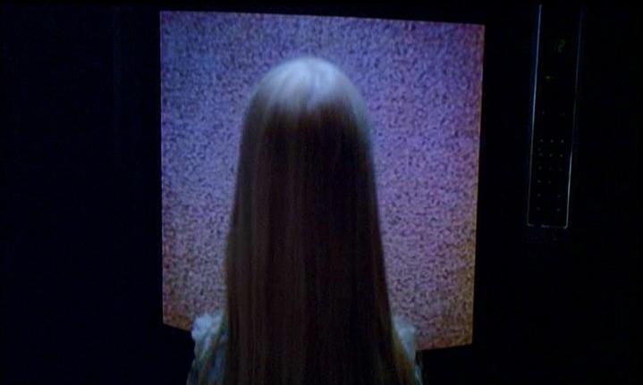 Heather O'Rourke si avvicina al televisore in una scena di POLTERGEIST: DEMONIACHE PRESENZE