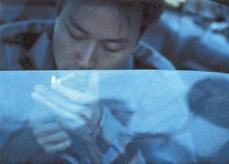 Leslie Cheung si accende una sigaretta in una foto di scena di Happy Together
