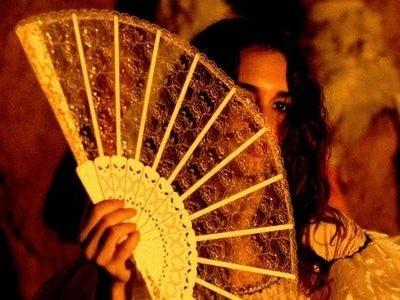 Una misteriosa Paz Vega si nasconde dietro un ventaglio in una scena di Per amare Carmen