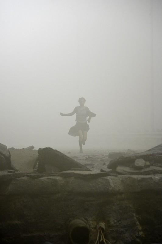 Radha Mitchell corre nell'inquietante nebbia di cenere in una scena di SILENT HILL