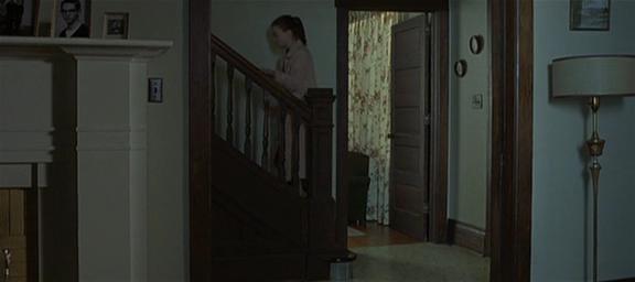 12.Inquadratura come alla 6, la ragazza ritrae la testa dalla stanza e si avvicina alle scale. Sale