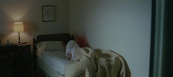 15.Controcampo verso l'interno della stanza. Un corpo sul letto, sangue sul muro