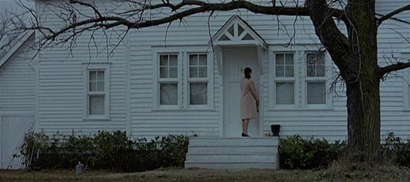 9.Torniamo in campo lungo, controcampo sulla ragazza che guarda la macchina e si volta verso la porta, decide di aprire