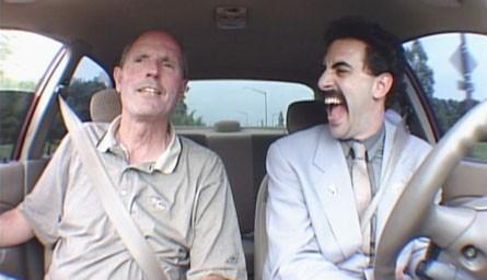 Sacha Baron Cohen accanto a un venditore di auto in una scena di 'Borat'