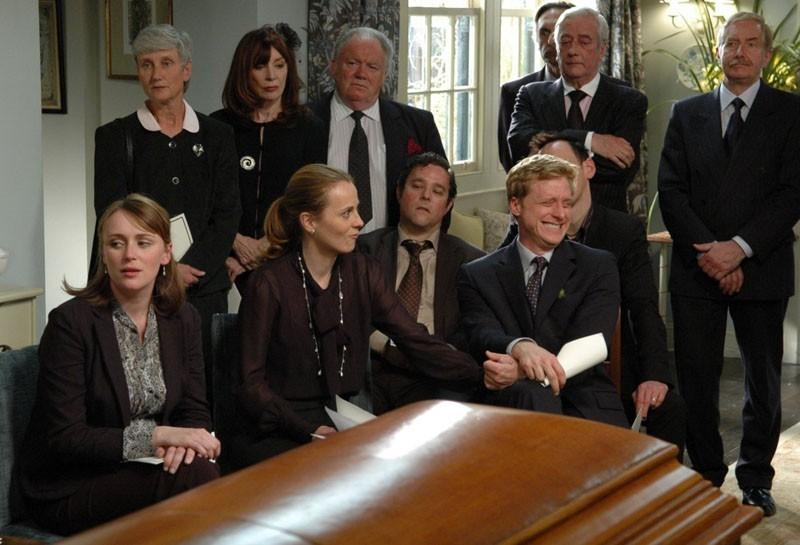 Il parentado riunito attorno alla bara in una scena del film Funeral Party