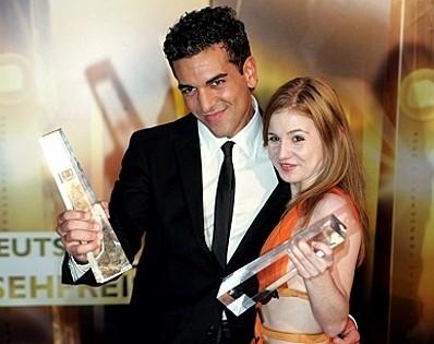 Elyas M'Barek riceve un premio insieme ad una collega attrice.