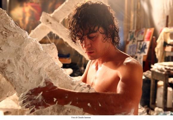 Riccardo Scamarcio al lavoro su un'opera d'arte in una sequenza del film Colpo d'occhio