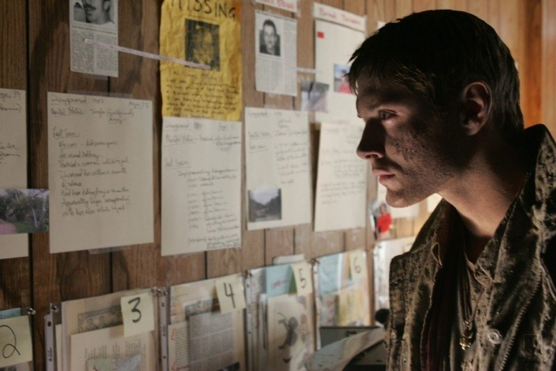 Jensen Ackels osserva gli indizi raccolti da suo padre appesi alla camera di motel nell'episodio 'la caccia ha inizio'