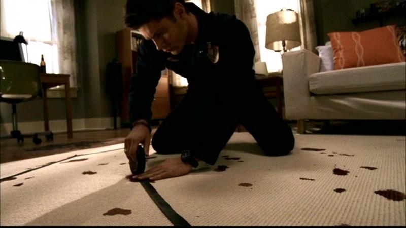 Jensen Ackles nel ruolo di Dean, ricostruisce un simbolo con del nastro adesivo, nell'appartamento dell'ultima vittima nell'episodio 'Ombre' di Supernatural