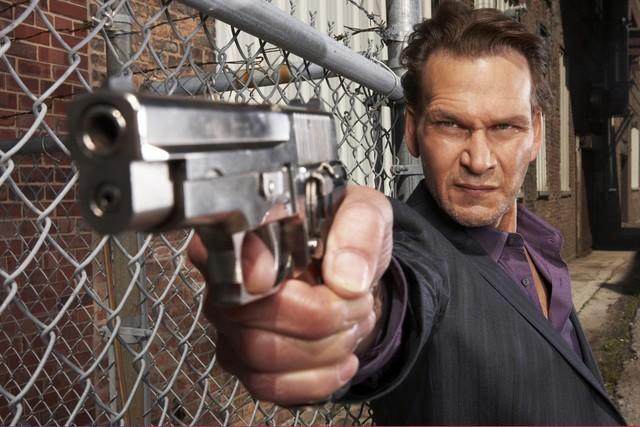 Patrick Swayze armato di pistola in una foto promozionale della serie The Beast