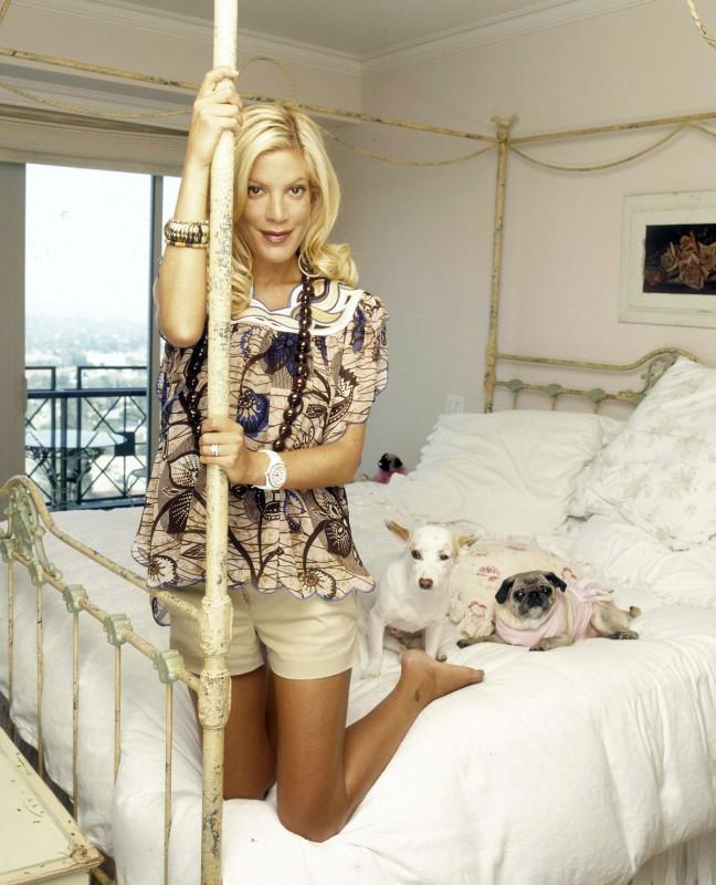 l'attrice Tori Spelling a piedi nudi sul letto