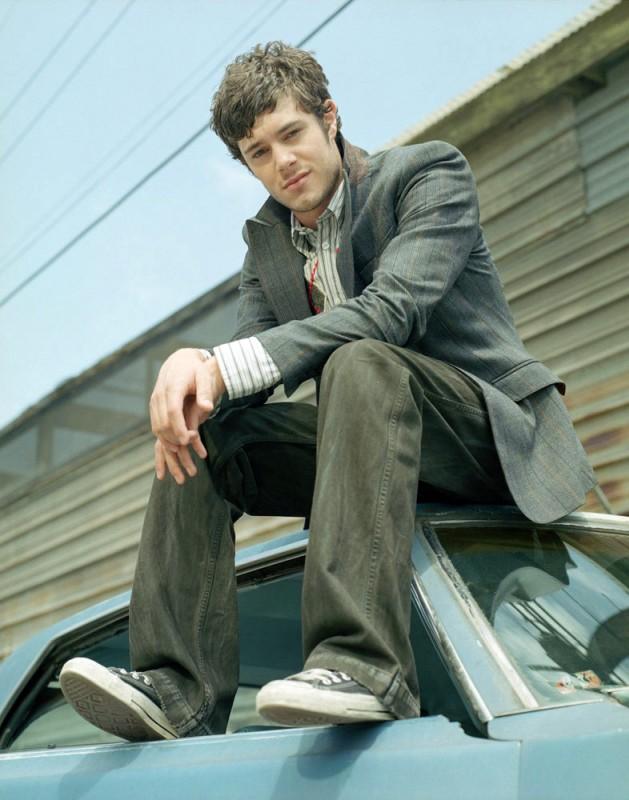 Adam Brody seduto sul tettuccio di un'auto