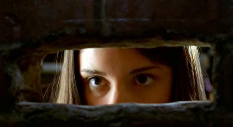 Liz Parker (S. Appleby) guarda attraverso un buco nel muro nell'episodio 'Il diario scomparso' di Roswell