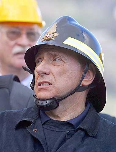 Silvio Berlusconi indossa un copricapo da vigile del fuoco