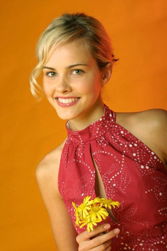 Una foto promozionale di Isabel Lucas con fiorellini gialli