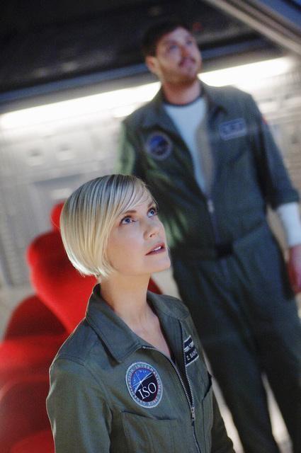 Laura Harris e Dylan Taylor (sullo sfondo) in una scena della serie Defying Gravity
