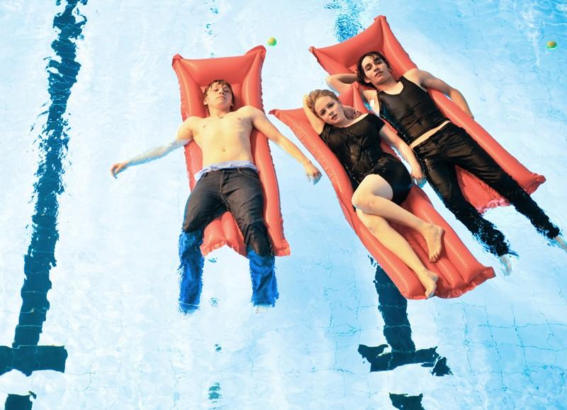 Rupert Grint, Kimberlye Nixon e Robert Sheehan sdraiati in piscina in una scena del film CherryBomb
