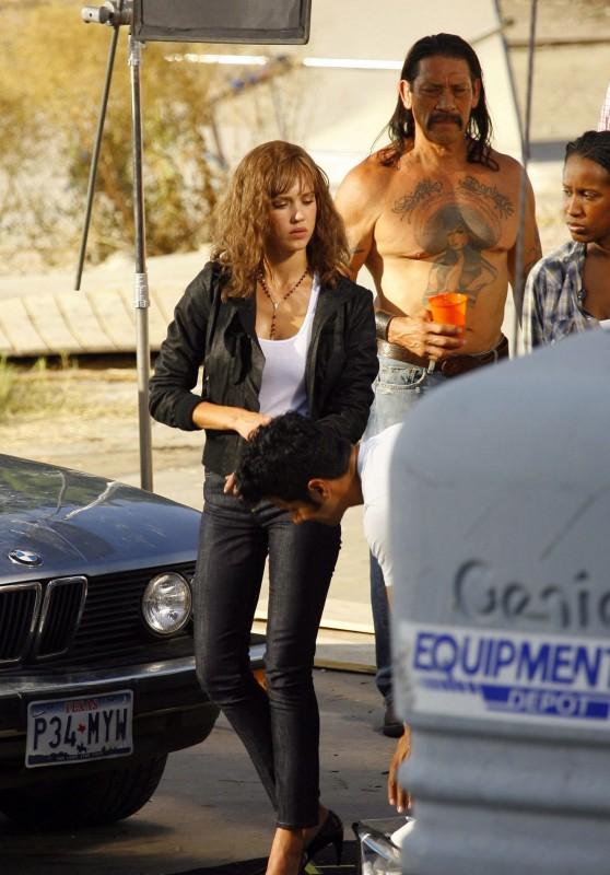Jessica Alba sul set di Machete insieme a Danny Trejo (alle sue spalle, con un vistoso tatuaggio sul petto)