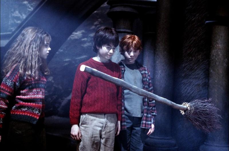 Emma Watson, Daniel Radcliffe e Rupert Grint osservano un manico scopa nel film Harry Potter and the Sorcerer's Stone