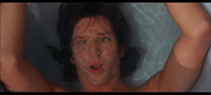 Michael Brandon a mollo nella vasca in una scena del film Quattro mosche di velluto grigio (1971)