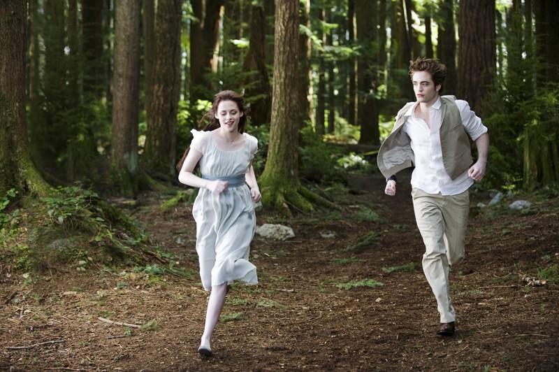 Bella (Kristen Stewart) corre nel bosco con il suo amato Edward (Robert Pattinson) nel film Twilight: New Moon