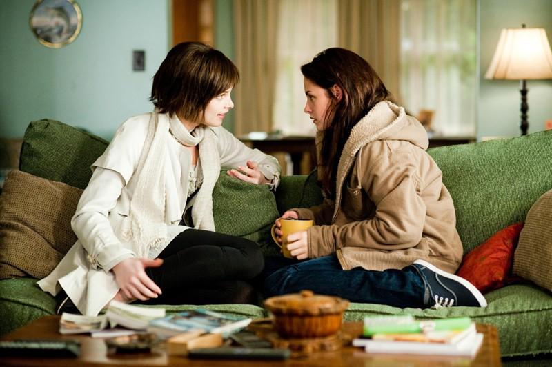 Alice (Ashley Greene) parla con Bella (Kristen Stewart) sedute sul divano nel film Twilight: New Moon