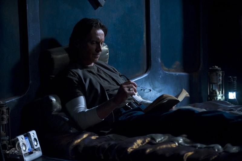 Il Dott. Rush (Robert Carlyle) legge un libro nell'episodio Light di Stargate Universe