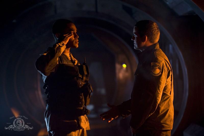 Justin Louis e Jamil Walker Smith si salutano nell'episodio Light di Stargate Universe