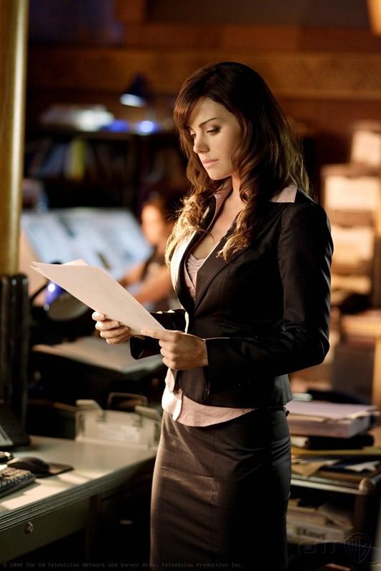 Lois (Erica Durance) legge un documento in una scena dell'episodio Crossfire di Smallville