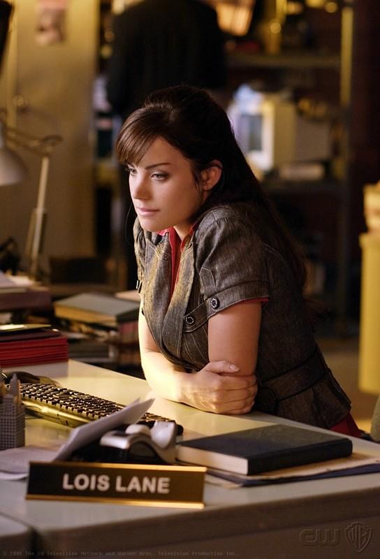 Una pensierosa Lois Lane (Erica Durance) alla scrivania nell'episodio Crossfire di Smallville
