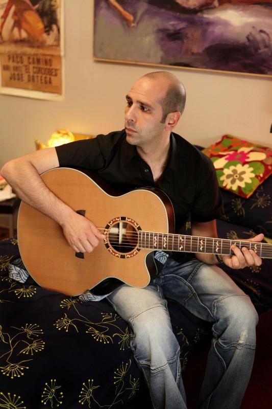 Checco Zalone (Luca Medici) con la chitarra nel film Cado dalle nubi