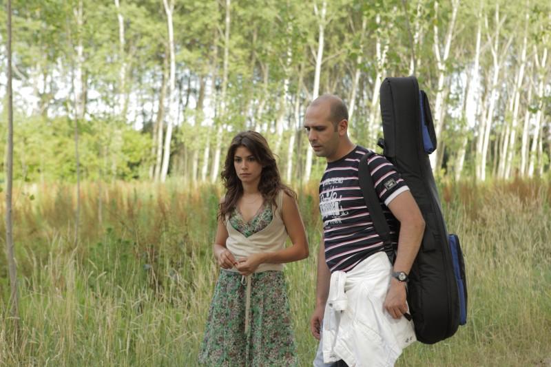 Chitarra in spalla per Luca Medici in una scena di Cado dalle nubi, il primo film di Checco Zalone