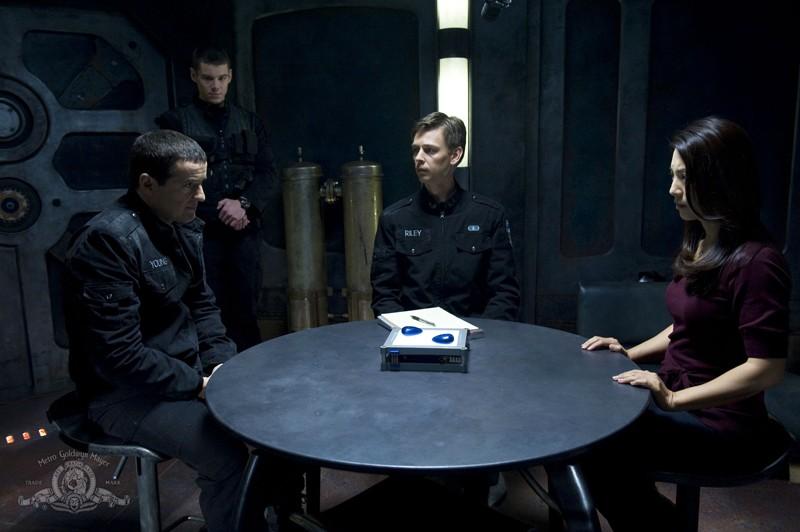 Justin Louis, Haig Sutherland e Ming-Na seduti al tavolo con le pietre dell'episodio Earth di Stargate Universe