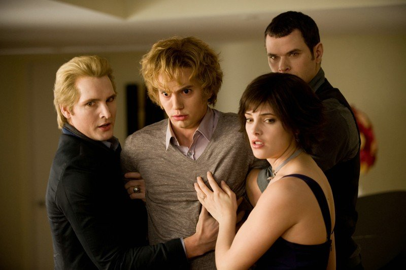 Peter Facinelli, Kellan Lutz e Ashley Green trattengono Jackson Rathbone in un momento del film New Moon