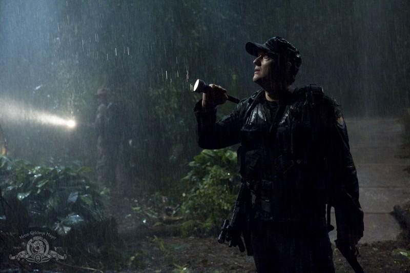 Il Colonnello Young (Justin Louis) sotto la pioggia, sul pianeta boscoso nell'episodio Time di Stargate Universe