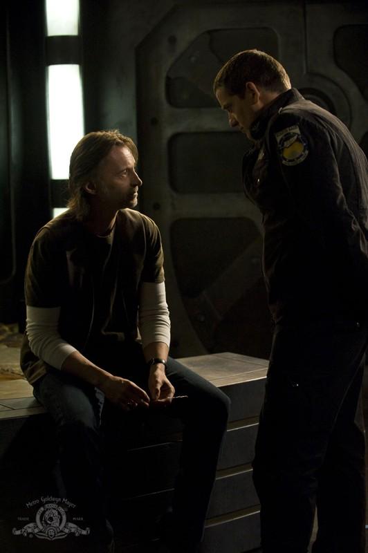 Justin Louis discute con Robert Carlyle in una scena dell'episodio Life della serie Stargate Universe