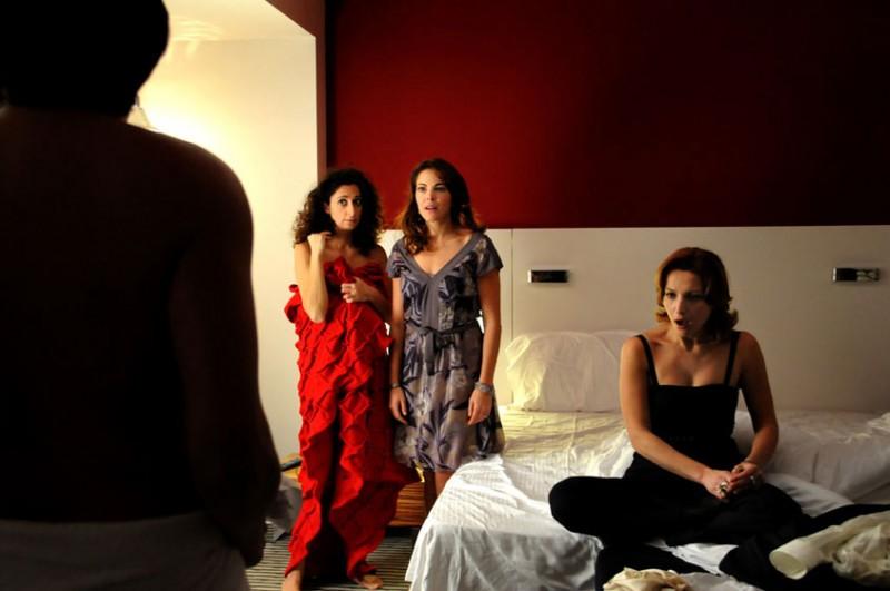 Claudia Gerini (seduta sul letto) in una sequenza del film Meno male che ci sei, di Luis Prieto