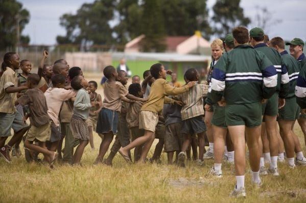 Matt Damon e i bambini del Sud Africa in una scena del film Invictus