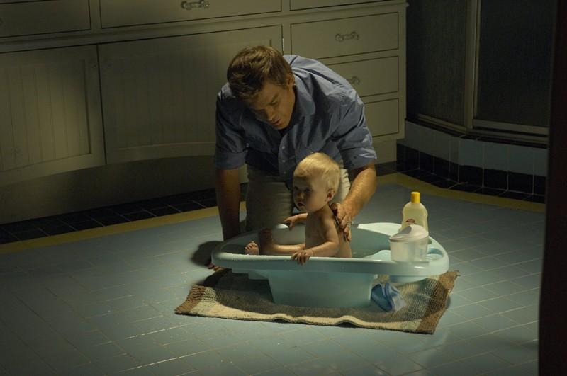 Dexter (Michael C. Hall) fa il bagnetto al suo bambino nell'episodio Lost Boys di Dexter