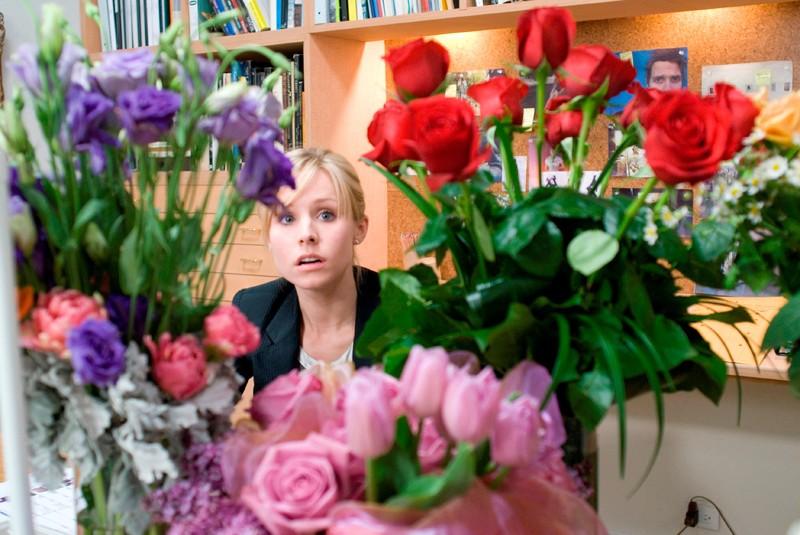 Kristen Bell dietro a degli splendidi fiori colorati in una scena di When in Rome