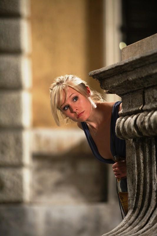 Una scena del film When in Rome con Kristen Bell che spunta da dietro un monumento