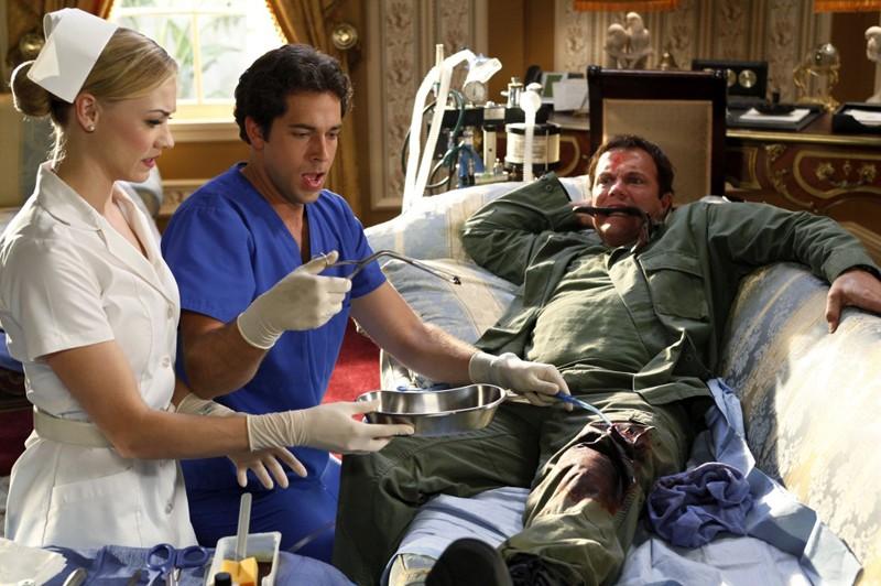 Zachary Levi e Yvonne Strahovski estraggono il proiettile dalla gamba di Adam Baldwin nell'episodio Chuck Vs. The Angel de la Muerte