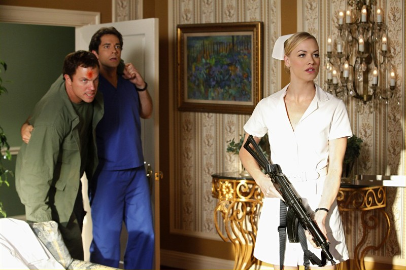 Zachary Levi sostiene Adam Baldwin ferito, vicino a Yvonne Strahovski armata di mitra nell'episodio Chuck Vs. The Angel de la Muerte