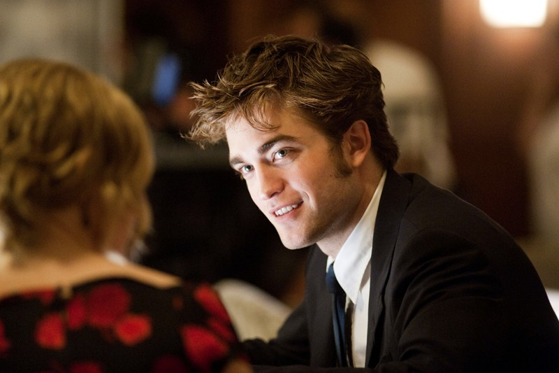 Robert Pattinson parla con Emilie de Ravin (di spalle) in una scena del film Remember Me