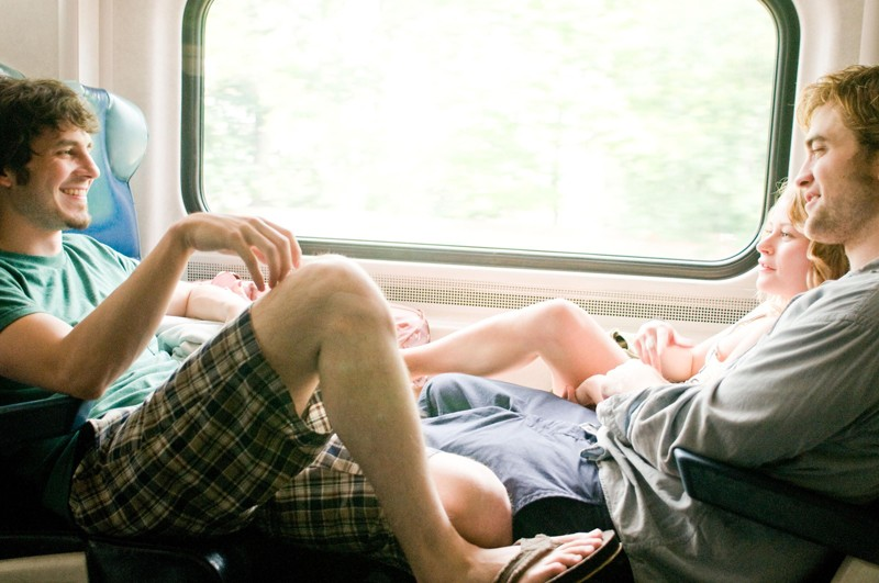 Aidan (Tate Ellington), Tyler (Robert Pattinson) ed Ally ( Emilie de Ravin) in una scena in treno nel film Remember Me