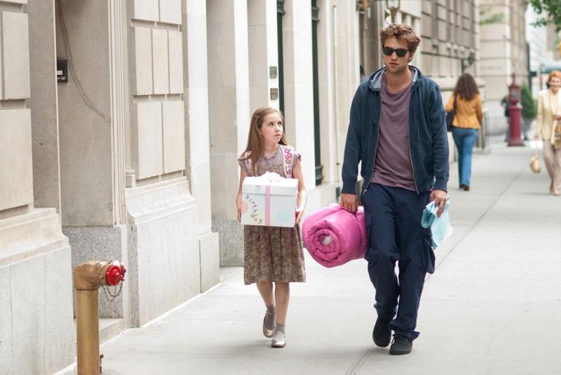 Ruby Jerins e Robert Pattinson passeggiano per strada in una scena del film Remember Me