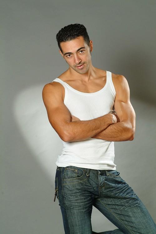 Un ritratto dell'attore Anis Gharbi in jeans e canotta.