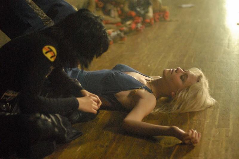 Dakota Fanning sdraiata a terra e con l'amica Kristen Stewart nel film The Runaways