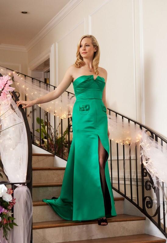 La graziosa Caroline (Candice Accola), in abito verde, scende la scalinata in una scena dell'episodio Miss Mystic Falls di Vampire Diaries